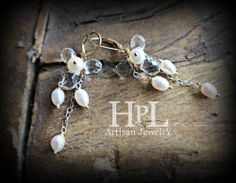 """faceted clear quartz are wrapped with gold fill wire.the earrings are  2 1/2""""  longfreshwater pearls accent and drop like water drops from the 3 quartz petalsYour earrings will arrive carefully presented in my HPL Jewelry pouchperfect for  this season and all year long!"""