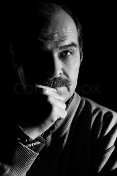 Colourbox.com Stock image of 'Stodio portrait of adult man over black background. Low key, black and white image'