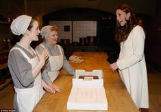 In the kitchen: The Duchess chats to actresses Sophie McShera (Daisy) and Lesley Nicol (Mr...