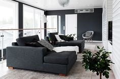 Modern living room with charcoal sectional, white slat walls, and a wood floor lamps.