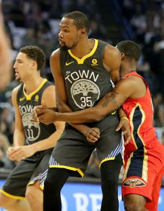 Golden State Warriors' Kevin Durant (35) is held by a New Orleans Pelicans' player in the first half of an NBA game at Oracle Arena in Oakland, Calif., on Saturday, April 7, 2018. (Ray Chavez/Bay Area News Group)
