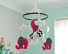 Pink Baby Elephant Mobile Welcome to FlossyTots This Elephant Mobile is READY TO SHIP This mobile consists of 2 white elephants and 2 Fuchsia Pink elephants with black and white chevron/polka dot fabrics on the ears, made with premium wool blend felt. Above each animal is a cloud.
