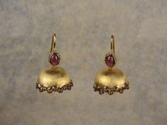 Simple jhumkis, handcrafted in sterling silver exude the warmth of the reds and oranges in garnets and citrines respectively.