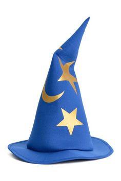 Conjunto de disfraz en punto suave con motivo de aluminio. Capa con cuello alto y cierre autoadherente. Sombrero de mago y varita mágica.