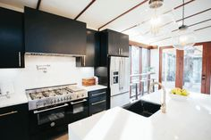 Chip and Jo installed new black cabinets, appliances, a waterfall island, marble countertops and backsplash, and brass hardware. Simple pendant lights from Shades of Light offer a timeless look over the island. The walls were painted Pure White for a clean finished look.