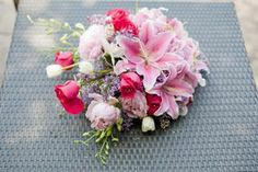 Cascading Jewel Bridal Bouquet with stargazer lilies, hot pink roses, pink peonies, lilac, white dendrobiam orchids and tulips. For more awesome bridal bouquet ideas check out http://www.weddingflowerbuzz.com/Bridalbouquets.html *created by Naturally Beautiful Floral Designs