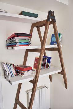Libreria realizzata recuperando una vecchia scala. Visto il poco spazio ho pensato che fosse interessante dare l'effetto che una parte della scala proseguisse nella parete. I ripiani sono di legno di riciclo ed i ferma libri di ferro con saldature a vista.