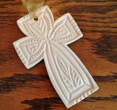 Hand carved and glazed in a bright white, this cross ornament will look great on your tree or as a wall hanging. The cross measures