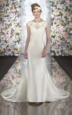 Elegant lace and silk fit-and-flare wedding gown features sprays of Diamante details on the bodice and silk-covered buttons on the back. Court train has beaded lace three dimensional detailing to match bodice.