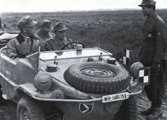 A officer in a VW Type 166 Schwimmwagen having a conversation with his men