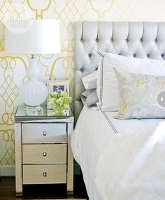 Graphic gold and white wallpaper, mirrored nightstands, white glass lamp, and faux fur throw give this beautiful bedroom a luxurious look.