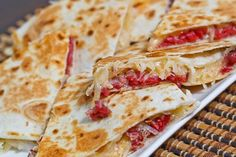 Reuben Quesadillas - 2 (8 inch) tortillas,  1/2 cup swiss cheese, shredded,  1/4 cup cooked corned beef, chopped or shredded and warm, 1/4 cup sauerkraut, squeezed and drained,  1/2 tablespoon russian dressing or thousand islands dressing