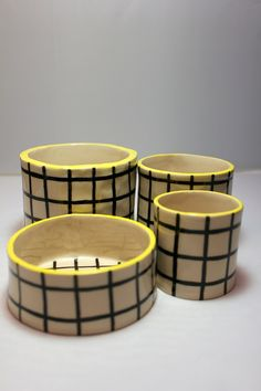 A smaller version of the 'Grid Pot' - this wee version is ideal for small  house plants as well as being the perfect size for tea lights. Made from  white stoneware, each pot is handmade and individually decorated with a  black and white minimal grid design and a bright yellow rim.  All of the ceramic products are completely unique and made and painted by  hand in Dundee. Please allow for slight imperfections in the work, it adds  to their unique charm!  Dimensions: approx. 5(H) x 5(W...