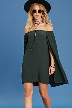 - A woven shift dress featuring off-the-shoulder short sleeves, elasticized shoulders, and a draped cape design.