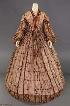 "PAISLEY PRINTED PURPLE DRESS, MID 1860s Purple sheer cotton organdy w/ paisley patterned vertical rows, CF bodice opening w/ ribbon trim, balloon sleeves & small cuffs, gathered full skirt, B 33"", W 27"", L 59"", (scattered tiny & small holes, underarms stained, repairs to shoulder & skirt back, hem edge dirty) fair."