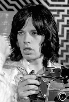 Mick Jagger with a Polaroid camera, photographed by Baron Wolman.