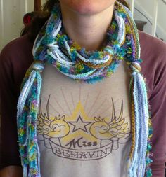 Easy crocheted scarf.  Chain about 18 or more very long chains(about 10 feet long to wrap around the neck twice).  Gather together and tie into knots at intervals that look appealing.  Good use of scrap yarns!