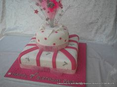 Hot pink and white two tier stacked parcel cake with pink stars and sugar straps. Silver sugar 7s and topped with a wired pink and silver feathered topper