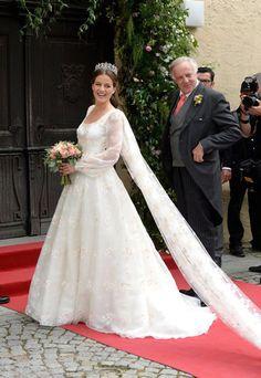 Luisa Beccaria foi a responsável pelo vestido de noiva. De mangas longas levemente bufantes, o modelo foi feito em organza, com flores bordadas em bege e tons bem clarinhos de rosa. No lugar de véu, o vestido tinha uma capa removível de 7 metros de comprimento.
