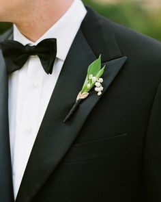 A sprig of lily of the valley and a faux gold leaf give this groom's lapels a special touch