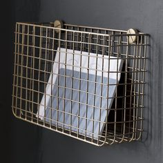 Shop Grid Brass Magazine Rack. Handcrafted from iron wire, modern grid finished in bright brass hangs on the wall to collect mail/magazines in the entry or supplies, etc in the office. Grid Brass Magazine Rack is a CB2 exclusive.