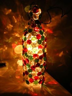 Love this idea- instead of using lights inside- use a candle and glass vase (instead of a bottle), any color glass stones glued to the outside. by sammsfamily