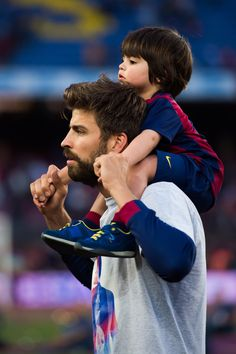 Gerard Pique of FC Barcelona carries his son Milan Pique after the La Liga match between FC Barcelona and RC Deportivo La Coruna at Camp Nou on May 23, 2015 in Barcelona, Catalonia.