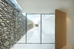 """Via thehardt Cefn Castell (2014) by STUDIO Stephenson situated in Criccieth, United Kingdom. The 1,883 ft² (175 m²) house plan is abstracted as a Mondrian inspired painting, which is hung at the heart of the house. The stone remains of a 400 year old cottage were re-used for the new boundary wall offering privacy and textural contrast of the 'traditional' juxtaposing 'the new'. The new house separates from the wall with a glass slot roof, visually suggesting the house delicately """"kisses"""" the…"""