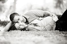 black and white photography maternity shot of husband and wife laying on grass