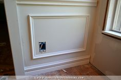 Attach frame to wall with adhesive and nailsl - How to install picture frame moulding wainscoting - addicted2decorating.com