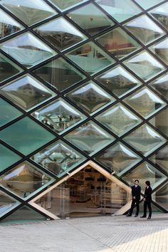 Prada Aoyama by Herzog & De Meuron.  Intentional glass warping, but still allows the views.  I wonder what drove the decision.