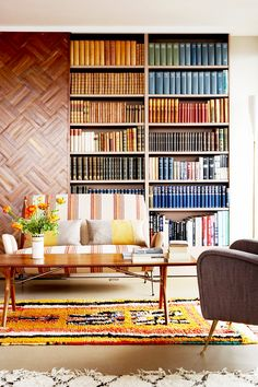 Color-coordinated library with striped love seat and yellow pillows