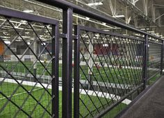 At this indoor soccer complex, the second floor mezzanine overlooks three fields. The woven wire mesh railing infill panels were designed using a square, Mesh that was turned on a 45 degree angle and welded to a steel tube. Gates And Railings, Metal Railings, Deck Railings, Stair Railing, Railing Ideas, Stairs, Front Fence, Fence Gate, Indoor Soccer Field