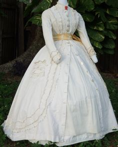 Amazing dress of white dimity worn open over a white muslin skirt. Shown with a period coral brooch and yellow silk sash c.1865