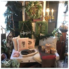 Repurposed an antique rusty crib into a daybed! Perfect for the porch...it has a waterproof crib mattress with a washable slipcover so it won't retain musty smells! Rustic and Refined corner of the shop..with blingy chandelier pairing with the rusty mirror and daybed. Chippy shutters, holiday greenery and ribbons, ticking pillows and bells complete the look! Oh...and blankets. Super for sitting around the firepit! American Decor, Crib Mattress, Daybed, Shutters, Slipcovers, Vignettes, Ribbons, Cribs, Greenery