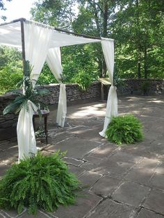 This chuppah is made from PVC pipe, covered with textured spray paint, and has simple curtains draped from it. Then simple greenery is first fastened with floral wire for security, then tied with a chair tie. Designed and created by Manchester (TN) Weddings By Design