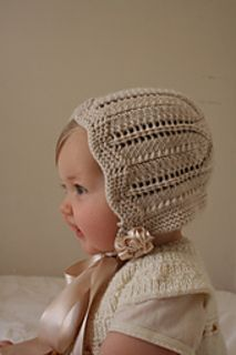 """Unashamedly retro, but so back in vogue, the prettiet little bonnet to frame and warm your little cherub's face. Made in medium-weight wool cotton yarn in a flattering shade of blush pink, the bonnet features the sweetest lacy design with a little star pattern at the crown. it is finished and tied with oversized bows in contrast ""café au lait"" sating ribbon. It coordinates with the bootees to make the perfect little gift set."""