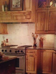 Oak cabinets with carerra back splash.