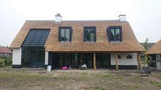 De combinatie tussen landelijk en modern is goed in balans. Wit landhuis met rieten dak. Alle kleuren zijn in balans.