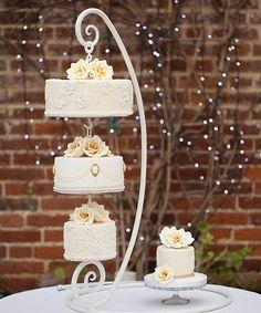 Torta colgada de base tipo candelabro de color balnco con rosas champán. #TortaDeBodas