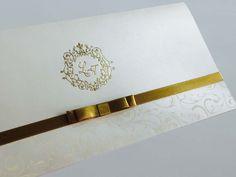 Convite personalizado de casamento de aba reta, branco e dourado, fechamento com laço também dourado.