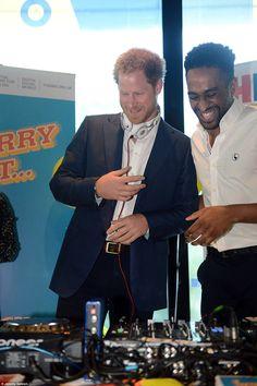 Prince Harry shares a joke with DJ AJ King as he tries his hand on the decks...