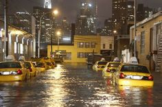 Taxi cabs line a flooded street in Queens