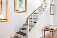 The designers created a more open and inviting landing to the lower level of the home. A custom railing on the existing stairs allows light from the main floor to drift downstairs. Powder-coated metal pairs with a white oak handrail.