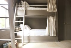 Urban Grace Interiors  2012 Ultimate Beach House - Interior Design by Erika Powell. Adorable boy's bedroom with gray built-in bunk beds, gray wood paneled walls, vintage locker wire basket and Studio Bon Textiles Fuzz Stone Fabric bolster pillows.