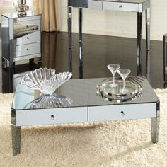 """Beautiful mirrored chic coffee table will add elegance to any living room decor and added storage with 2 drawers.     Features:  Crisp clipped corners on the tops and canted legs that taper sharply Rectangular shape High-end look is wrapped in smoked mirror and highlighted with knobs in a black chrome color Parisian collection 2 Drawers feature flush fitting drawers with narrow, polished bevel edges 15"""" H x 24"""" W x 47"""" D"""