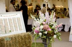 Beautiful flowers at entrance of marquee - Little Bidlake       #marquee   #flowers     #tableplan    #haybale