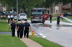 Ferguson police walk away from the crime scene as firefighters wash the blood of Michael Brown out of the street.