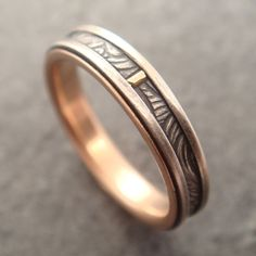 This beautiful wedding band is made from sterling silver and 14k rose gold. It features a sterling silver band inlaid with a sterling ribbon