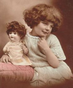 Girl with short curly hair and matching doll.